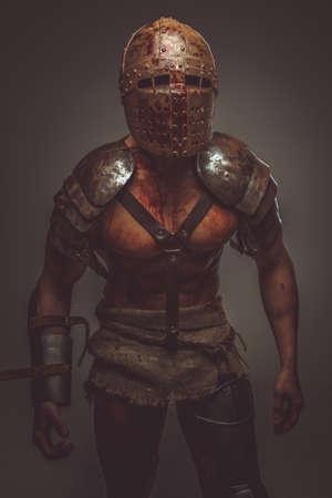 pezones: Gladiador Bloody con armadura y casco, sombras oscuras. Aislado en el fondo gris.