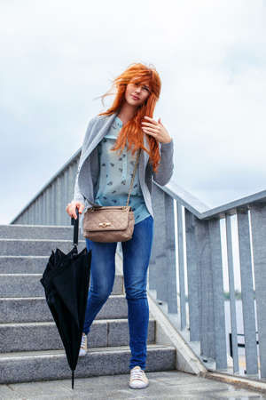 bajando escaleras: Mujer del Redhead con el paraguas negro caminando por las escaleras.