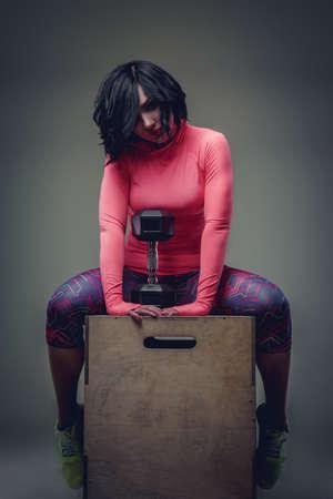 ropa deportiva: mujer morena impresionante en ropa deportiva de colores sentado en caja de madera y la celebración de mancuerna.
