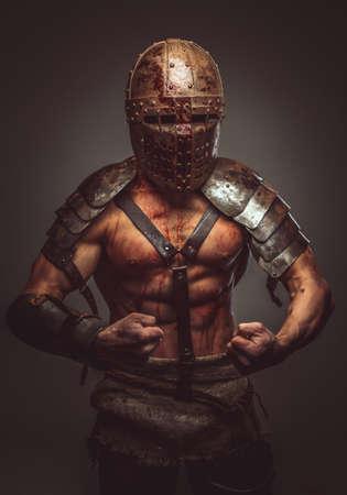 pezones: gladiador sangrienta enojado en el casco y armadura antigua. Foto de archivo