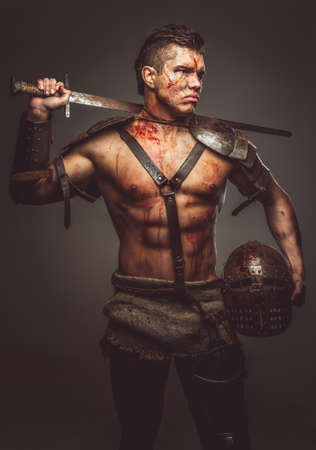 Muscular shirtless gladiator holding helmet and sword on his shoulder. Isolated on grey background.