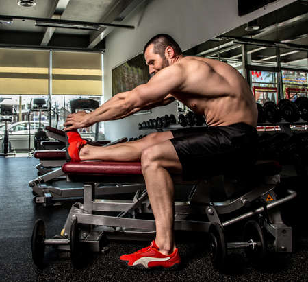 Shirtless bodybuilder doing exercises in a gym. photo