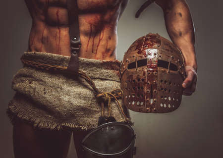 warrior sword: Bloody muscular torso and helmet of gladiator.