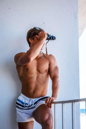 swimming shorts: Shirtless muscular guy in swimming shorts looking through binocular. Stock Photo