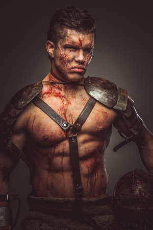 pezones: musculoso cuerpo de gladiador sangriento en armadura.