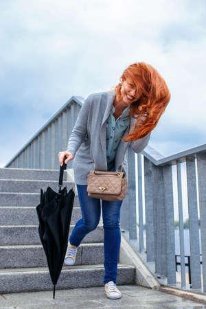 down stairs: Mujer del Redhead con el paraguas negro caminando por las escaleras.