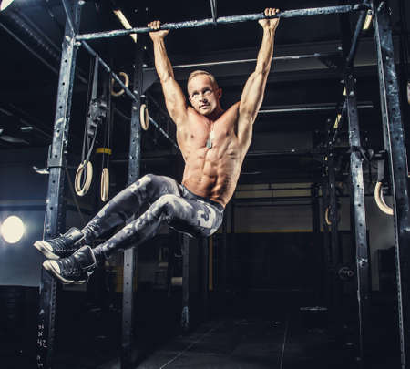 gripping bars: Shirtless muscular man in military pants doing exercises on horizontal bar.