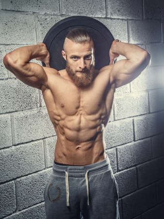 sixpacks: Shirtless muscular man with beard holding disk weight behind his head. Grey wall from bricks background.