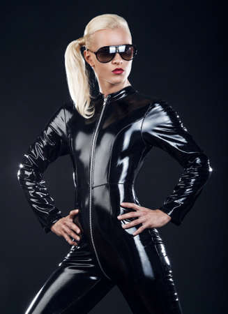 dominance: blond female in sunglasses and in latex black costume isolated on dark background. Stock Photo