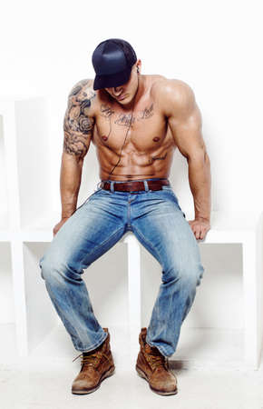 shirtless man: Shirtless muscular man with tatooes in blue jeans sitting on square podium over white wall.