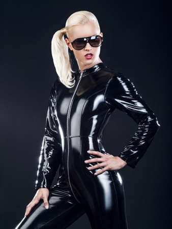 fetishistic: blond female in sunglasses and in latex black costume isolated on dark background. Stock Photo