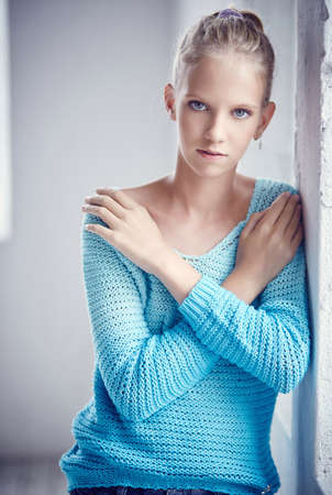 blue eyes: Attractive blond woman with blue eyes in blue jacket. Crossed arms.