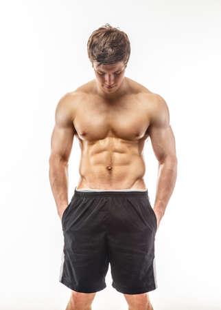 muscular: Tipo musculoso joven en pantalones cortos negros aislados en el fondo blanco.