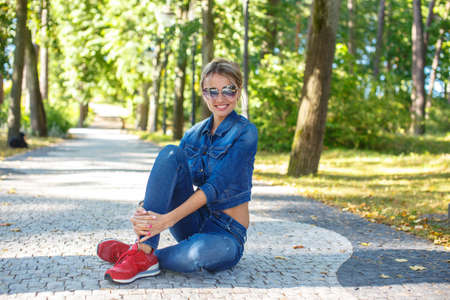 red jeans: Beautiful girl in jeans pants and jeans jacket sitting on the road in a park.