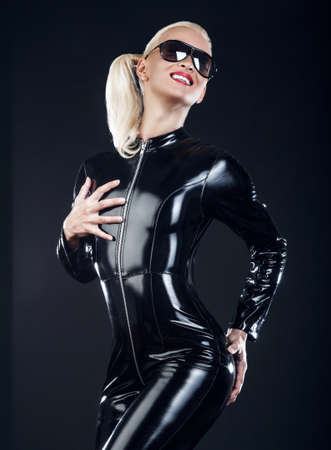 fetishism: blond female in sunglasses and in latex black costume isolated on dark background. Stock Photo
