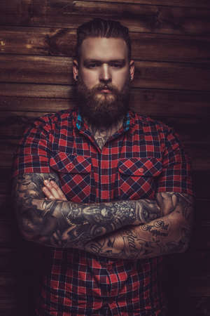 0a31aa868b634 Portrait of serious brutal man with beard and tattooes. Crossed arms. Stock  Photo