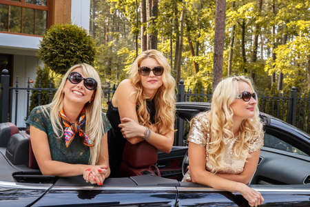 cabriolet: Three blond girls in sunglasses posing in a cabriolet car.