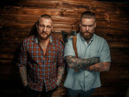 modelos posando: Dos sirve graves con barba y tatuajes que presenta sobre la pared de madera.