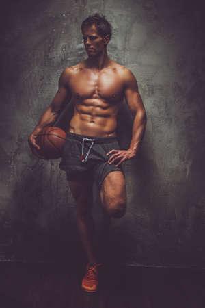 pezones: Jugador de baloncesto descamisado que presenta sobre la pared gris. Foto de archivo