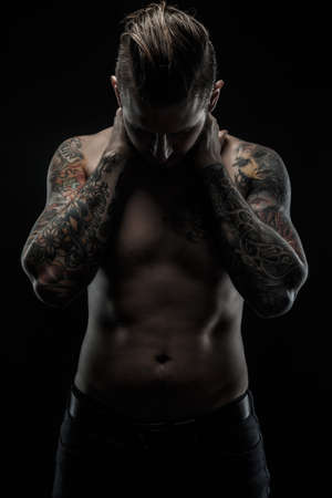 black shadows: Awesome man with tattoos posing in shadows over black background.