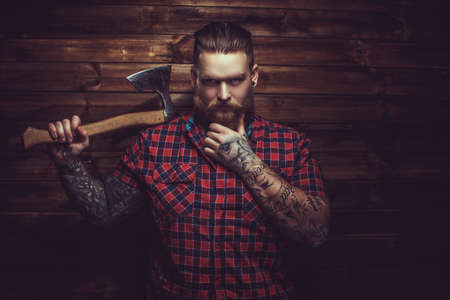 Brutal man with beard and tattooe holding axe over wooden wall.