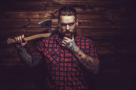 tatouage: Brutal man avec barbe et tattooe tenant hache sur mur en bois.