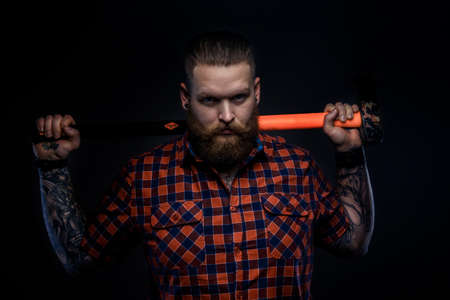 Serious man with beard and tattoo holding hummer on his shoulders. Isolated on dark background.
