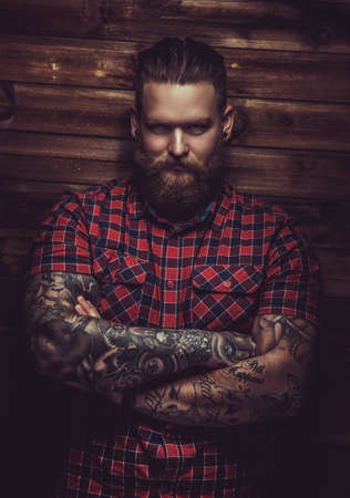 Portrait of serious brutal man with beard and tattooes. Crossed arms. Standard-Bild