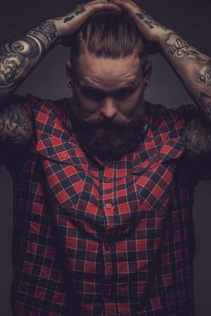 Brutal guy with beard and tattooes holding his head. Isolated on grey background.
