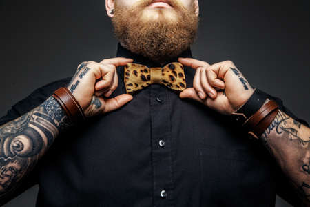 Part of man's face with beard and tattooed arms.