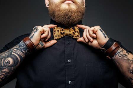 hombre calvo: Parte de la cara del hombre con la barba y los brazos tatuados.