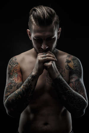 enticement: Portrait of shirtless man with tatooed body. Isolated on black background.