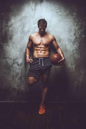 pezones: Masculino muscular impresionante en pantalones cortos grises que sostienen baloncesto y posando sobre fondo gris.