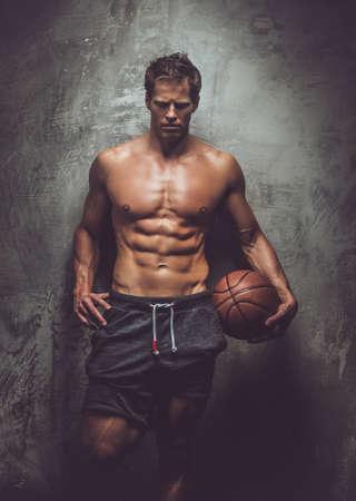poses de modelos: Masculino muscular impresionante en pantalones cortos grises que sostienen baloncesto y posando sobre fondo gris.