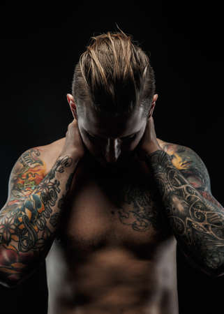 Awesome man with tattoos posing in shadows over black background.