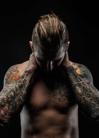 capelli lunghi: Impressionante con i tatuaggi in posa nelle ombre su sfondo nero.
