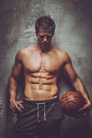hombre deportista: Jugador de baloncesto descamisado que presenta sobre la pared gris. Foto de archivo