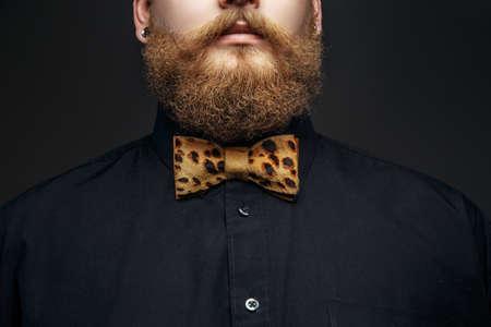lazo negro: Parte de la cara del hombre con la barba roja. Camiseta negro y corbata de lazo leopardo. Aislado en el fondo gris.