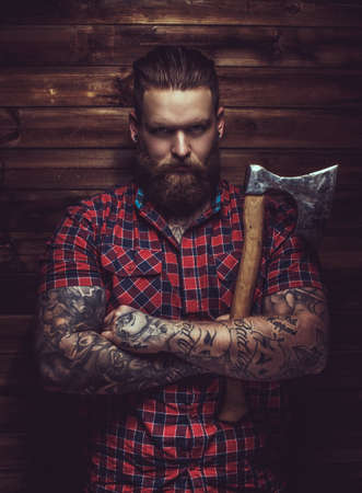 a beard: Brutal man with beard and tattooe holding axe over wooden wall.