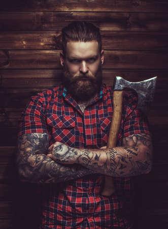 Brutale mens met baard en tattooe houden bijl over houten muur. Stockfoto