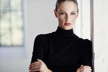 Portret van luxe donkerbruine vrouw in zwarte sweater over heldere achtergrond.