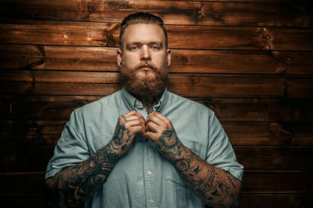 lumberjack shirt: Brutal man with beard and tatoos possing over wooden wall.