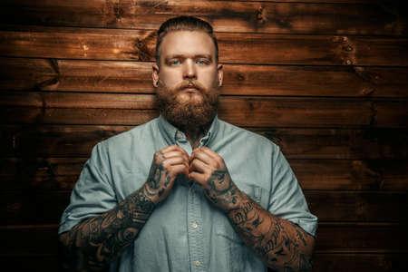 Brutal Mann mit Bart und Tatoos possing über Holzwand. Standard-Bild - 46987399