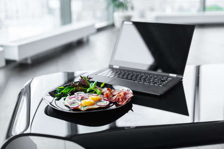 glance: Glance table with laptop and morning meals from eggs on dark plate.
