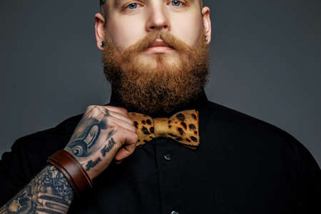 black t shirt: Man with beard in black t shirt and leopard bow tie isolated on grey background.