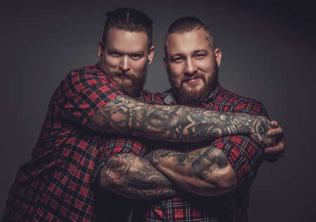 Two smiling friends with beards and tattooes on arms. Isolated on grey background. Foto de archivo