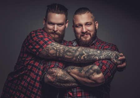 Twee lachende vrienden met baarden en tattoos op wapens. Geïsoleerd op grijze achtergrond.