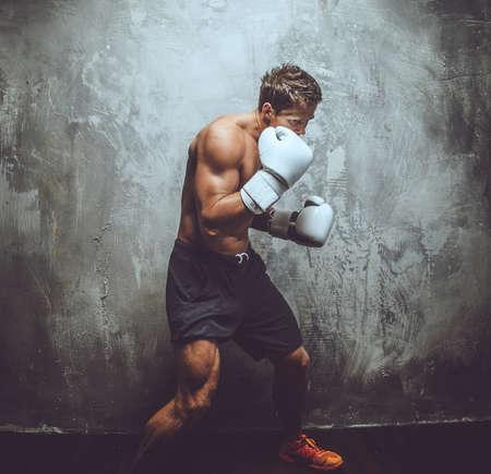 guantes: Fighter en blanco guantes de boxeo sobre la pared gris.