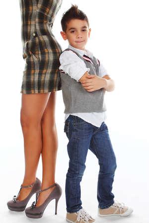 boy lady: Fashionable boy posing near womans legs on white background.