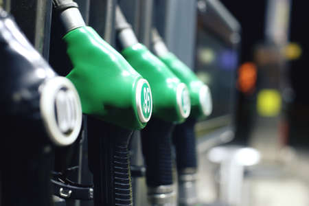 economy: Green fuel pistols on fuel station. Stock Photo